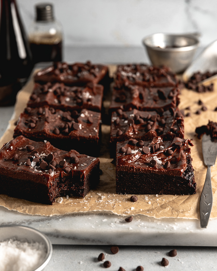 Marble cutting board with parchment paper and 8 sliced brownies topped with chocolate chips and sea salt.
