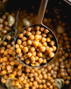 a ladle of chickpeas above a pot of chickpeas