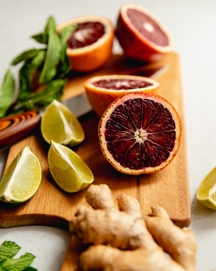 A cutting board with the ingredients for this cocktail recipe, including blood orange halves, lime wedges, a piece of ginger, and mint leaves.