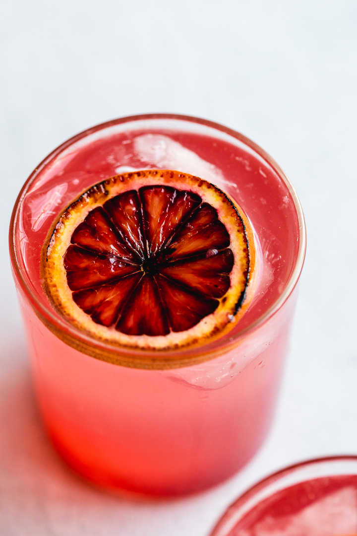 A 3/4 angle view of a blood orange gin smash with a slice of burnt blood orange floating on top.