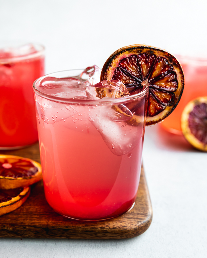 This seasonal gin cocktail features juicy blood oranges, fresh mint and lime, and sparkling water. A blood orange gin smash is the perfect cocktail for a winter afternoon. For a fun twist, you'll torch the blood oranges with a little sugar and add a smoky depth of flavor to this vegan cocktail recipe.